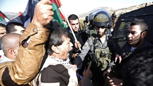 Palestinian minister Ziad Abu Ein (C) argues with Israeli border policemen during a protest near the West Bank city of ...