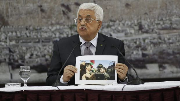 Palestinian President Mahmoud Abbas shows a picture of Palestinian minister Ziad Abu Ein as he is grabbed by an Israeli ...