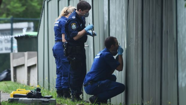 Police forensic officers go over the crime scene.