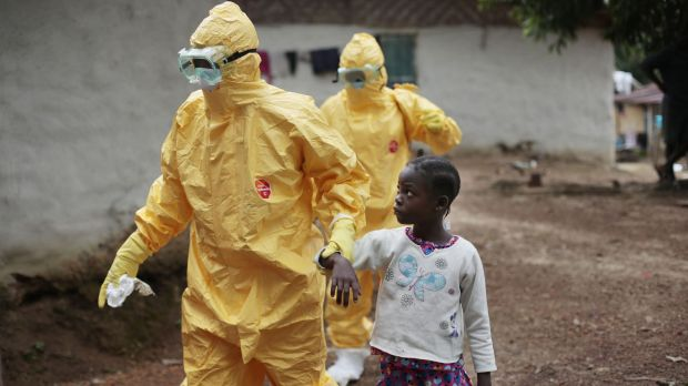 Hand and glove: Nine-year-old Nowa Paye is taken to an ambulance after showing signs of Ebola infection in the village ...
