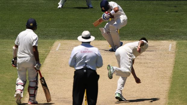 High hit: Virat Kohli is struck on the helmet by a Mitchell Johnson delivery.