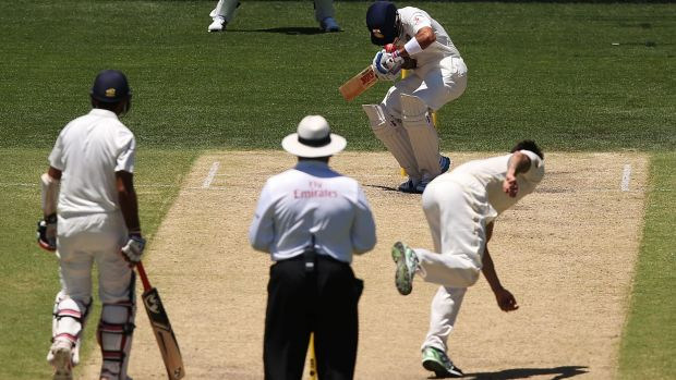 Helmet hit: Virat Kohli is struck on the helmet by a Mitchell Johnson delivery.