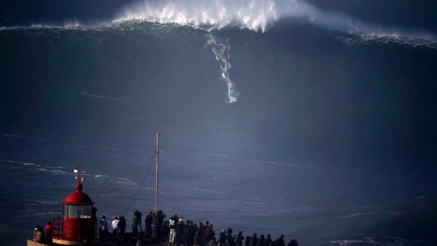 Crowds gather at Praia do Norte in Portugal to watch big-wave surfers tackle a monster swell.