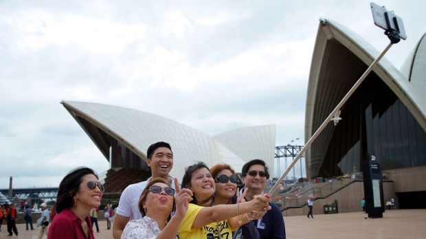Happy snap: Audrey Amparo uses a selfie stick to photograph her family at the Opera House.