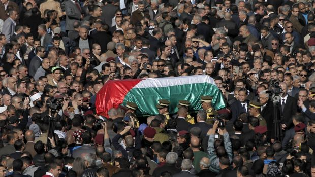 The coffin of Ziad Abu Eid is borne aloft during his funeral in the West Bank city of Ramallah.