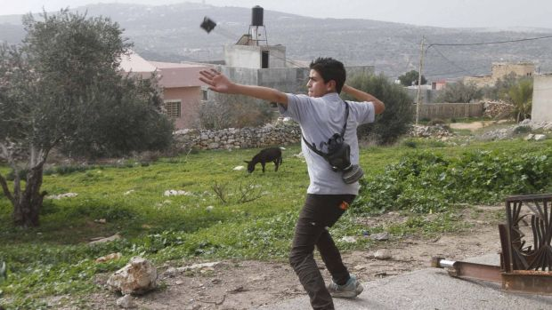 A Palestinian protester uses a slingshot to throw stones at Israeli soldiers during clashes following a protest against ...