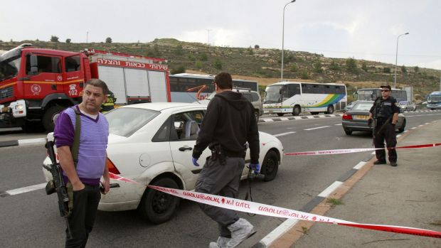 Israeli security forces inspect the scene of an acid attack by a Palestinian hitchhiker on an Israeli family outside the ...