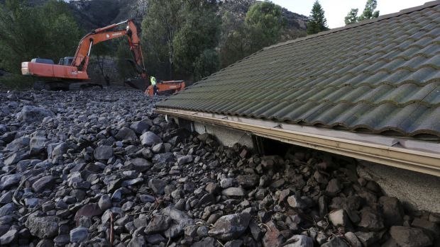 Covered up: Rocks reach the roof of a home after a mudslide struck at least eight homes during heavy rains in Camarillo ...