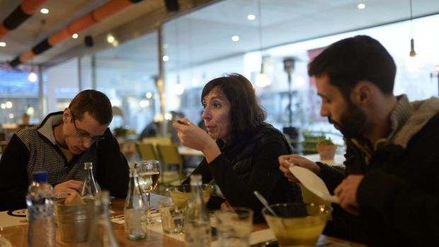 Time out: Simona Levi, 48, from Italy, centre, Sergio Salgado, 35, left, and Alfa Sanchez, eat in a restaurant during ...