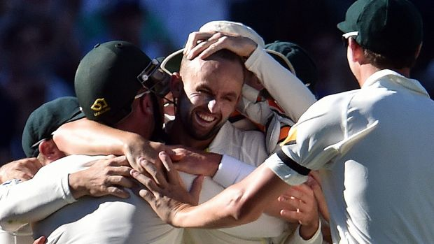 Nathan Lyon is mobbed by Australian teammates after bowling his side to victory against India in Adelaide.