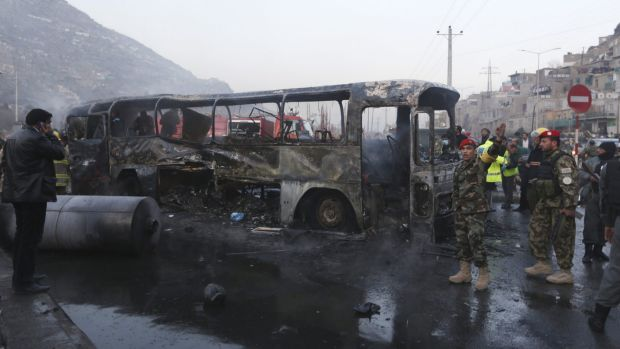Afghan security guards inspect the damaged bus at the site of a suicide attack.