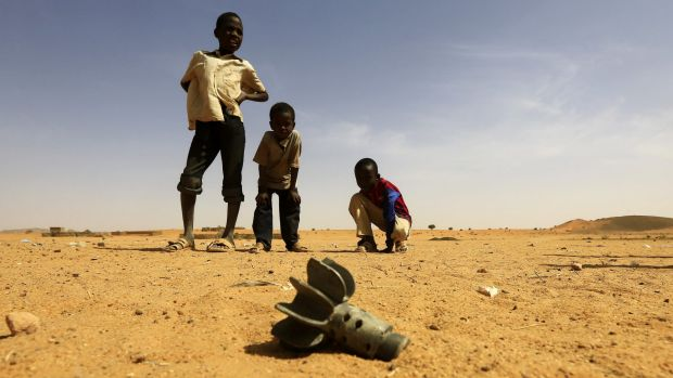 Children stand near the fin of a mortar at the al-Abbasi camp for internally displaced persons in Sudan's Darfur region.