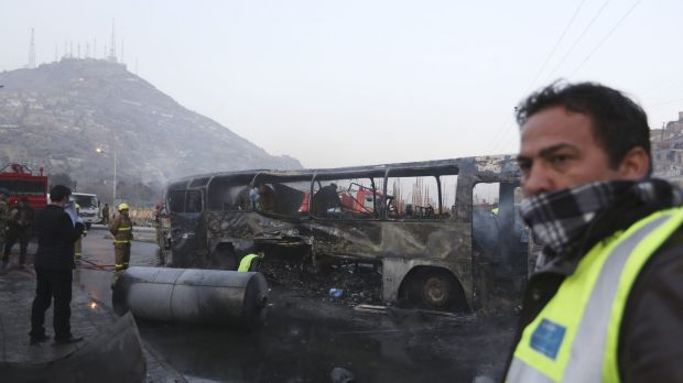 Afghan security guards inspect the remains of a bus after a suicide attack by the Taliban claimed the lives of six ...