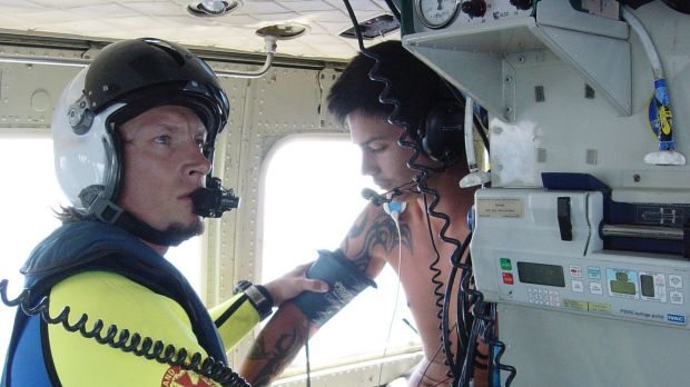A 20-year-old man receives care aboard an RACQ Careflight helicopter after being bitten by a shark while on a tuna boat ...