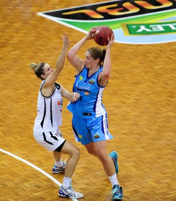 Left, Townsville Fire player Stephanie Cumming and Canberra Capitals player Sam Norwood in action.