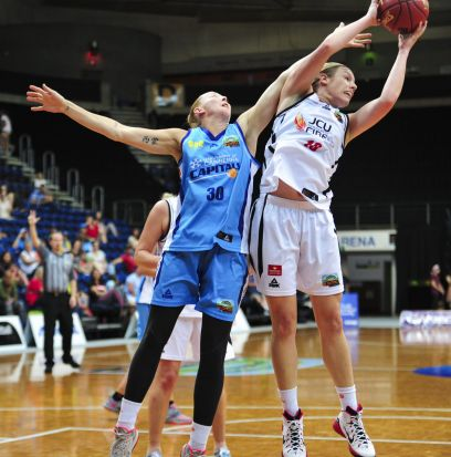 From left, Canberra Capitals player Michelle Cozier and Townsville Fire player Mia Newley in action.