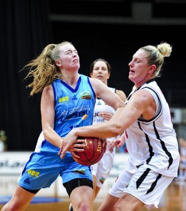 From left, Canberra Capitals player Abbey Wehrung and Townsville Fire player Suzy Batkovic in action.