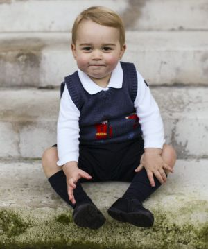 Prince George sits for his official Christmas picture in a courtyard at Kensington Palace in London, England.