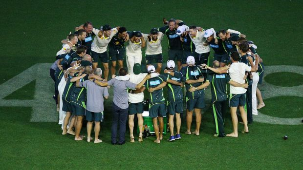 The Australian team and support staff celebrate after an emotional win.