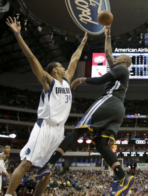 Dallas Mavericks forward Brandan Wright (left) defends against a shot by Golden State Warriors' Marreese Speights in the ...