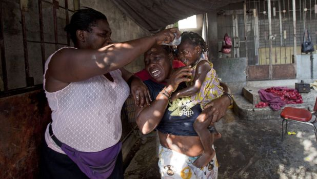 A little girl's face is washed after National Police fired tear gas near her home during protests in Port-au-Prince.