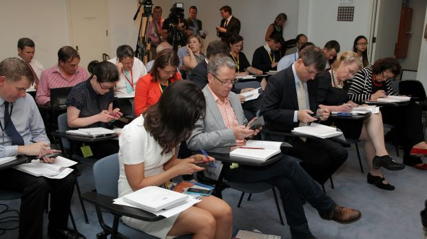 Journalists read their copies of the MYEFO ahead of the update from the government.