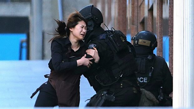 One of the women held hostage inside the cafe for several hours runs into the arms of police after being freed.