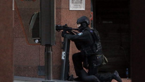 A NSW Tactical Operations Group police officer maintains his position at the scene in Martin Place, Sydney.