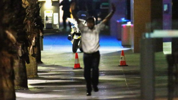 A hostage runs down Philip Street after coming out of the Lindt Cafe.