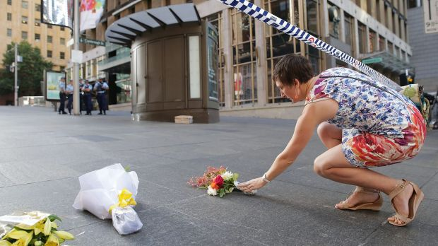 A woman cries as she leaves flowers to pay her respects at Martin Place.