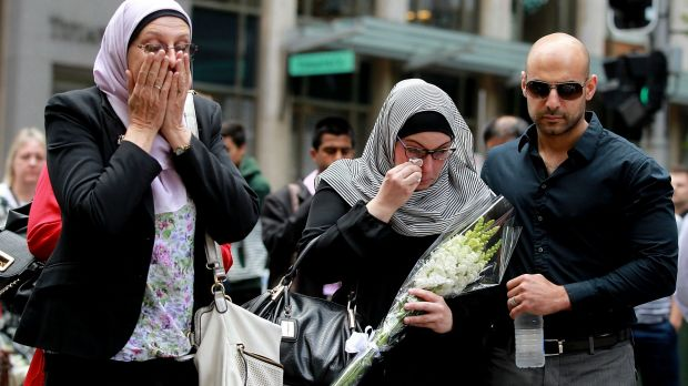 Members of the Muslim community lay flowers at Martin place after 2 people and gunman died when the Siege ended at 2am ...