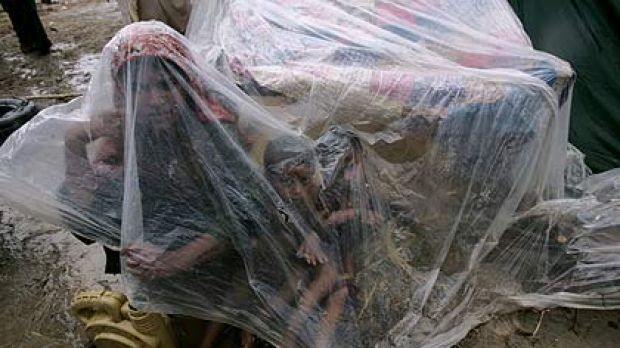 A family huddle under plastic as they wait for help to evacuate to safety along a road in Shekarpur, Pakistan.