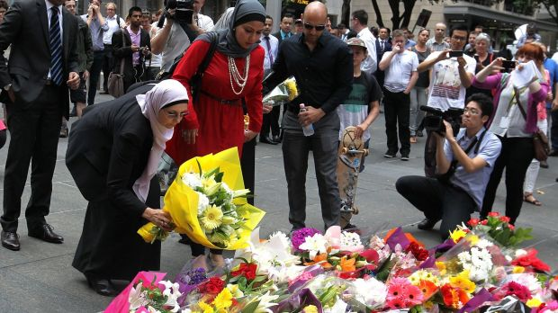 All together: Members of the Muslim community lay flowers at Martin Place.