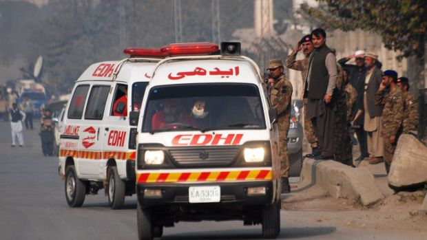 Ambulances leave a military-run school where Taliban gunmen have taken hostages.