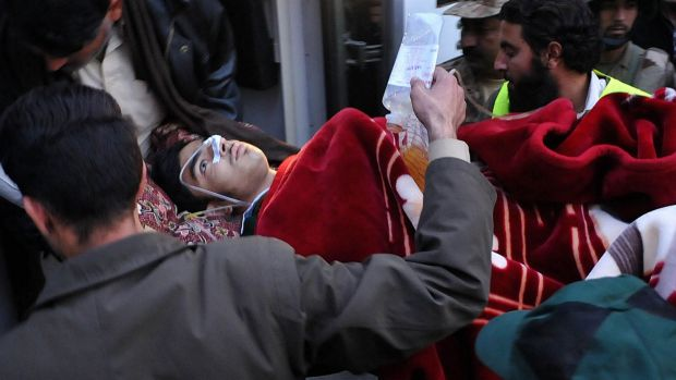 Medical support: Pakistani men transport a wounded student to hospital after Taliban gunmen attacked the school in ...