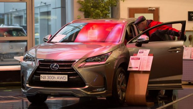 Will this hold value? A customer inspects a car for sale at a Lexus automobile dealership in Moscow.