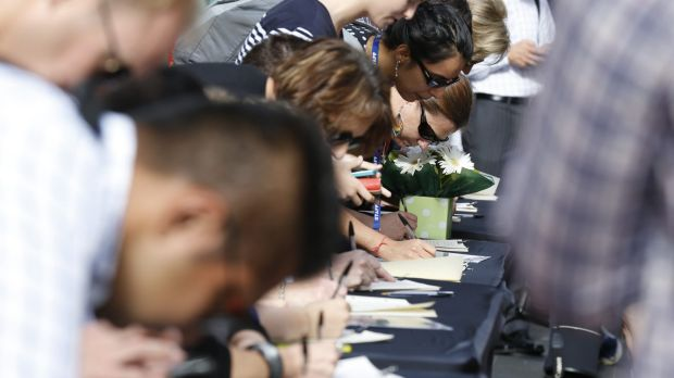 Outpouring: Hundreds are lining up to sign the condolence books at Martin Place.
