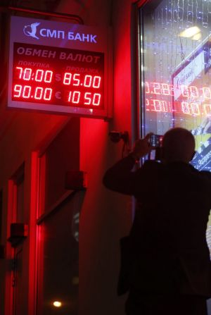 A shocked man takes a picture of a board showing currency exchange rates in Moscow on Tuesday.