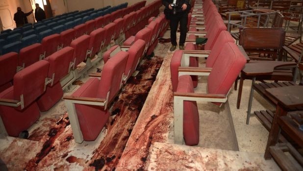 A Pakistani journalist takes a photo of the bloodied floor in the ceremony hall where many children were gunned down.