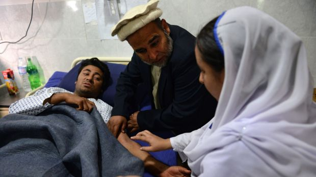 A Pakistani health worker treats an injured student at a hospital a day after an attack by Taliban militants at an ...