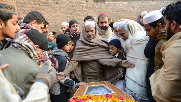 Pakistani mourners gather around a coffin during the funeral ceremony for victims of an attack by Taliban militants at ...