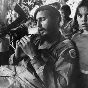 Fidel Castro as Cuban revolutionary leader relaxing at a sugar plantation near Havana, surrounded by children. Communist ...