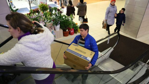 Panic buying: Russians in St Petersburg  grab bargains, fearing prices will rise due to the falling rouble.