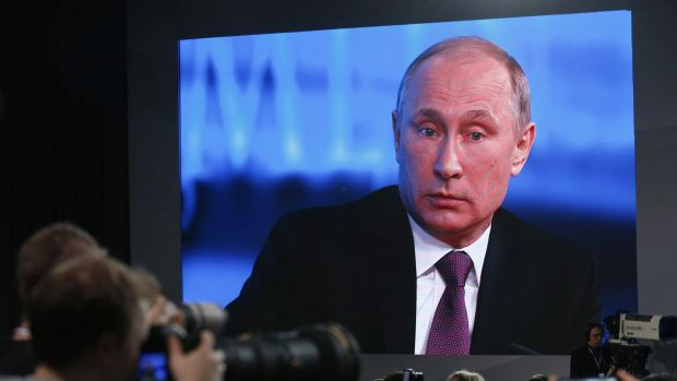 Vladimir Putin is seen on a screen during his annual end-of-year news conference in Moscow.