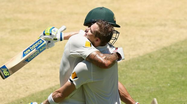 Steve Smith and Mitch Johnson embrace after Smith brings up his century.