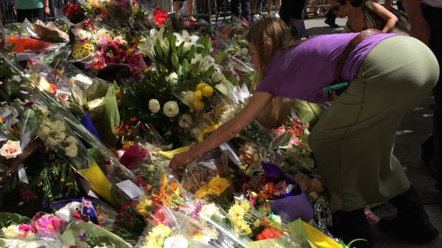 Joanne Proctor spreads sage ashes at the memorial outside the Lindt cafe.
