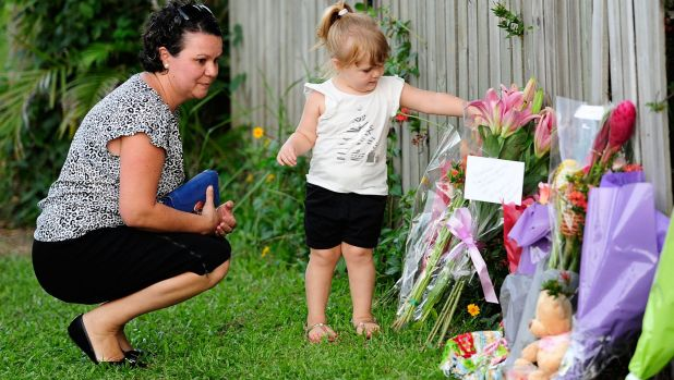 Members of the Cairns community leave flowers.