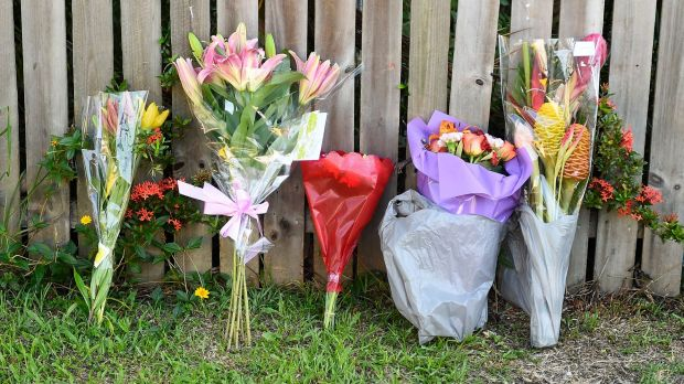 Flowers against a fence across the road from the scene of the multiple stabbing in Manoora.