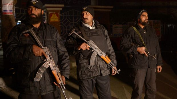 Pakistani police commandos stand guard during a rally in support of the 140 victims of the army run school shooting in ...