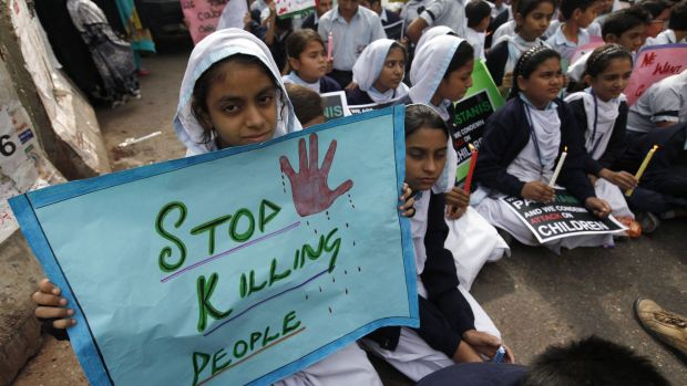 Students sit while holding placards and candles for the victims of the Taliban attack on the Army Public School in Peshawar.
